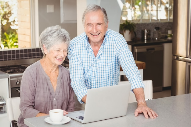 Happy senior man standing besides wife with laptop