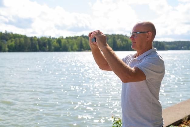 Счастливый старший мужчина фотографирует с телефоном на берегу озера