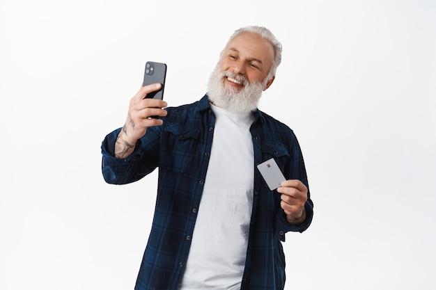 彼のクレジットカードで自分撮りをしている幸せな年配の男性、スマートフォンアプリの顔idでオンラインで支払うように笑って、インターネットショップで買い物をし、白い壁に立って