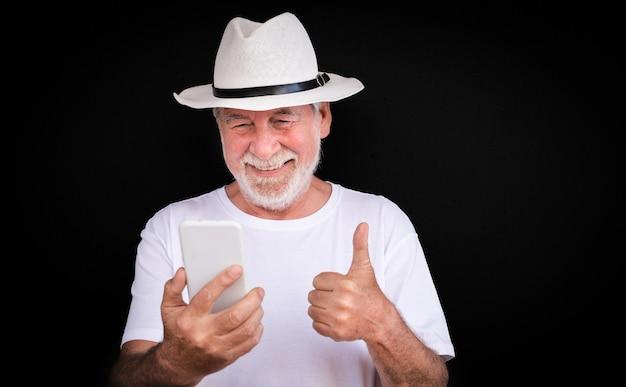 Счастливый старший мужчина с помощью мобильного телефона в видеозвонке с семьей. новые молодые люди, седые, привлекательные пенсионеры, наслаждающиеся свободным временем и технологиями. черный фон