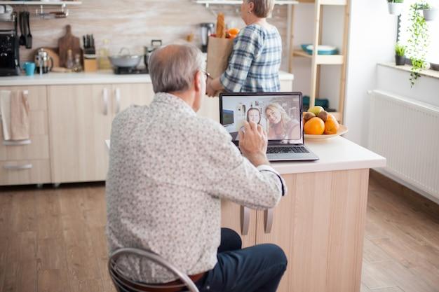 부엌에서 노트북을 사용하여 가족과 화상 회의를 하는 동안 조카에게 손을 흔드는 행복한 노인. 딸과의 온라인 통화. 현대 통신 온라인 인터넷 웹 기술을 사용하는 노인.