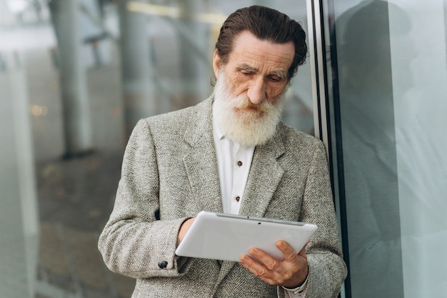 Happy senior man with the tablet on the office buildings