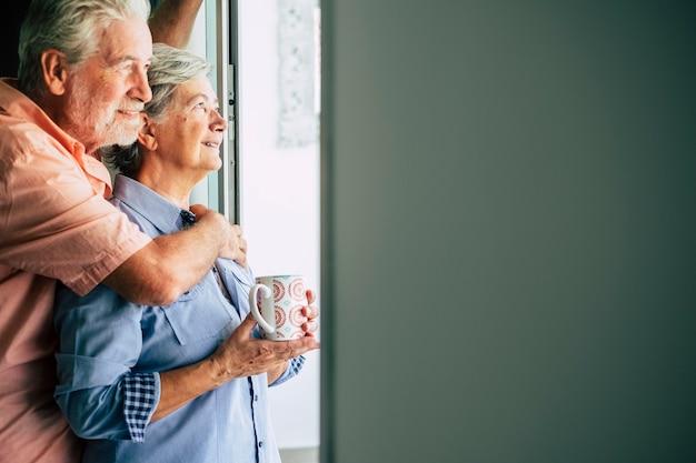 ドアの窓の外を見て家で優しく恋をしている幸せなシニア成熟したカップル-永遠に一緒に人々の老人と女性の概念
