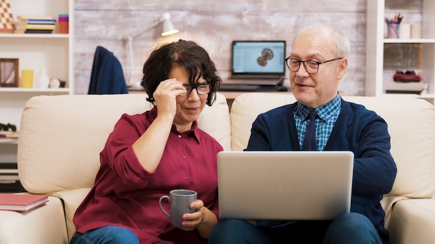 Happy senior middle aged couple sitting on sofa waving at laptop during a video call.