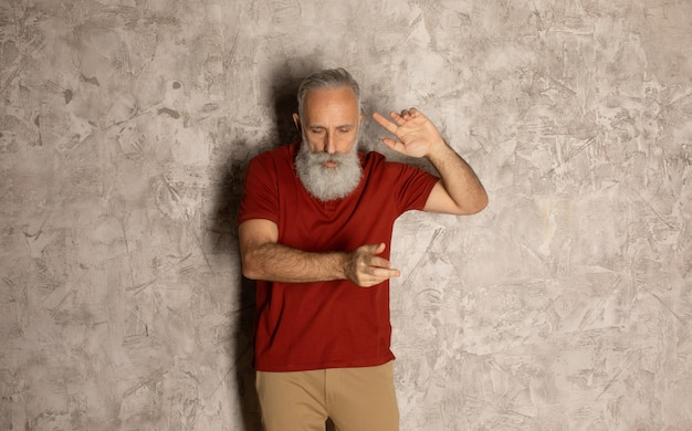 Happy senior millionaire man dancing on grey background.
