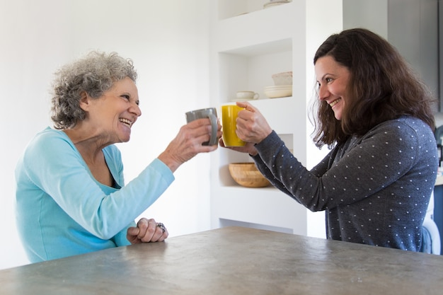 Happy senior mother and adult daughter toasting tea