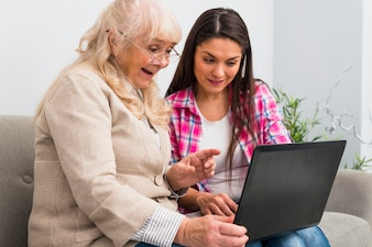 Happy senior mother and daughter looking at laptop