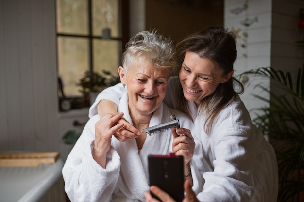 A happy senior mother in bathrobe with adult daughter taking selfie indoors  home selfcare concept