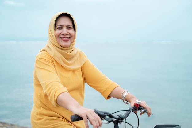 Happy senior muslim female riding a bicycle