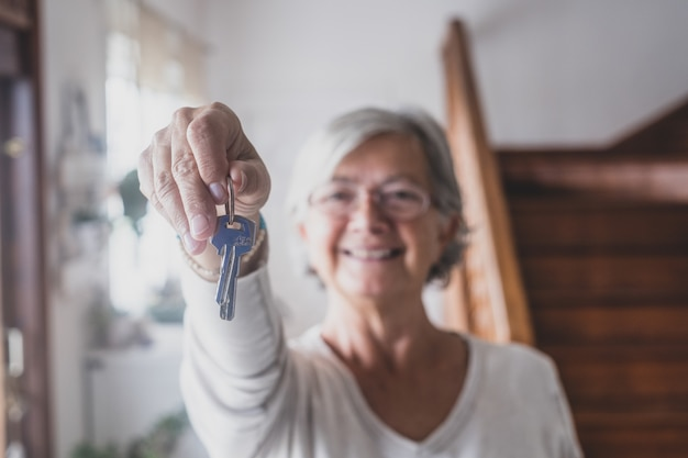 Happy senior old aged woman customer landlord hold key to new house apartment give to camera, older retired female hand real estate owner make sale purchase property deal concept, close up view