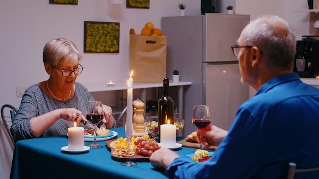 식탁에 앉아 레드 와인을 마시고 이야기하는 행복한 노부부. 집에서 웃고 있는 중년의 중년 가족이 함께 낭만적인 저녁 식사와 즐거운 대화를 나누며 즐거운 시간을 보내고 있습니다.