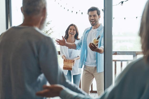 Счастливые старшие родители встречают молодую пару внутри дома