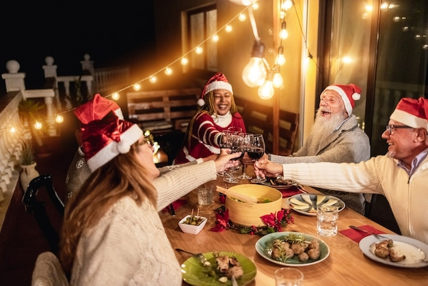 Happy senior people cheering with wine during christmas dinner at home wearing santa clause hats - focus on hands holding glasses