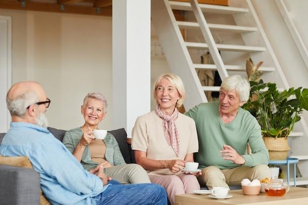 ソファに座ってお茶を飲み、部屋でお互いに異なる話をしている幸せな高齢者