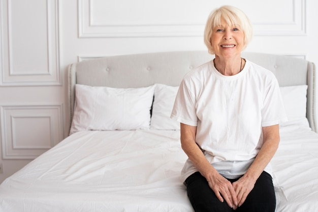 Happy senior sitting on bed