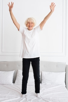 Happy senior standing on bed