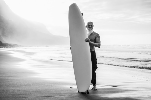 日没時にビーチでサーフボードを保持している幸せなシニアサーファー-顔に焦点を当てる