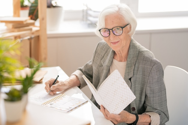 Happy senior white-haired businesswoman with open book making notes in notebook while reading by desk