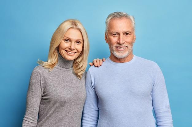 幸せな年配の女性と男性は、青い壁に隔離された愛の中で一緒にポーズをとる前向きな感情を表現します