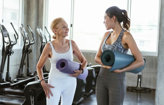 행복 한 고위 여자와 요가 체육관에서 젊은 십 대. 건강한 생활 방식을 운동하십시오.