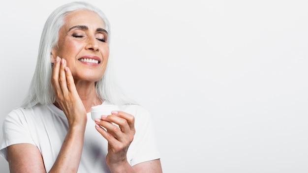 Happy senior woman applying cream