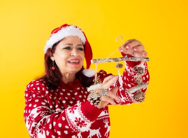 Happy senior woman christmas decorations yellow background