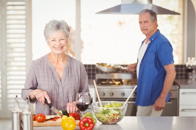 Happy senior woman cutting vegetables with husband in background