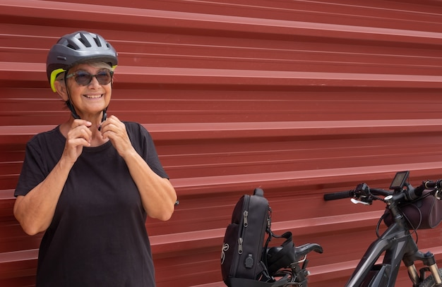 Happy senior woman cyclist in outdoor excursion close to a red metal panel  healthy lifestyle