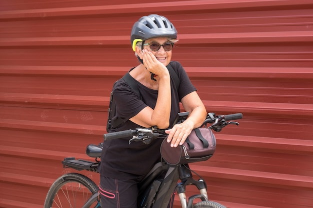 Happy senior woman cyclist in outdoor excursion close to a red metal panelhealthy lifestyle