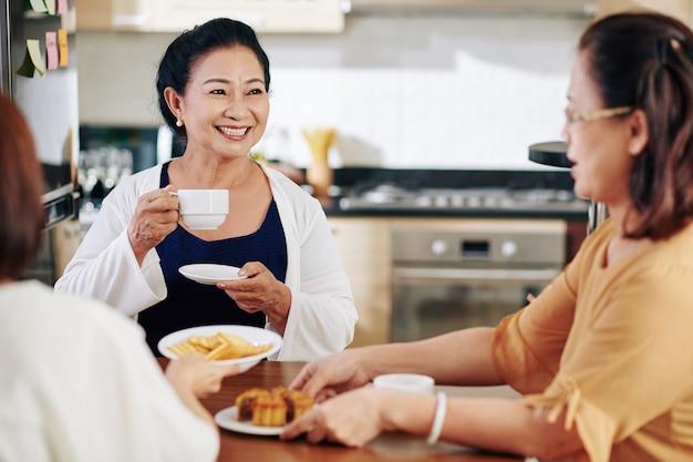 Счастливая старшая женщина пьет чай и ест печенье, наслаждаясь беседой со своими друзьями