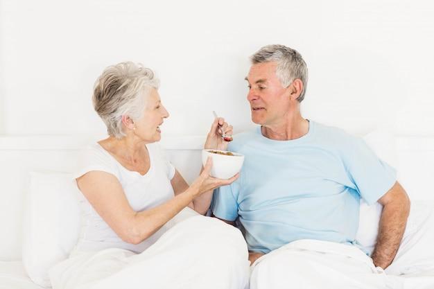 Happy senior woman feeding her husband at bed