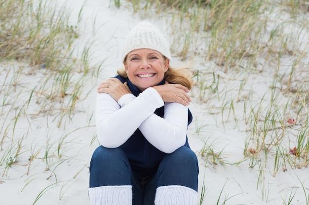 Happy senior woman feeling cold at beach