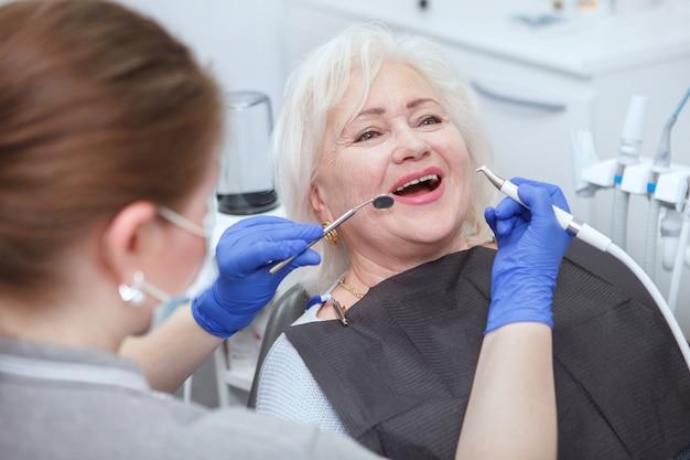 Счастливая старшая женщина, получающая стоматологическое лечение у профессионального стоматолога