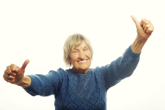 Happy senior woman giving two thumbs up as sign of approval. isolated on white.