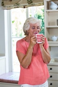 Happy senior woman having coffee in kitchen