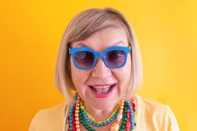 세련된 옷과 색안경 컨셉으로 즐겁게 노는 행복한 노년 여성