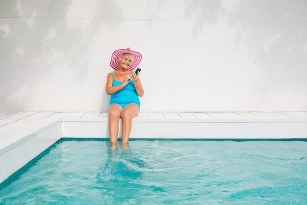 수영장에서 파티를 하는 행복한 노년 여성 - 여름철에 전용 수영장에서 일광욕을 하고 휴식을 취하는 아름다운 노부인