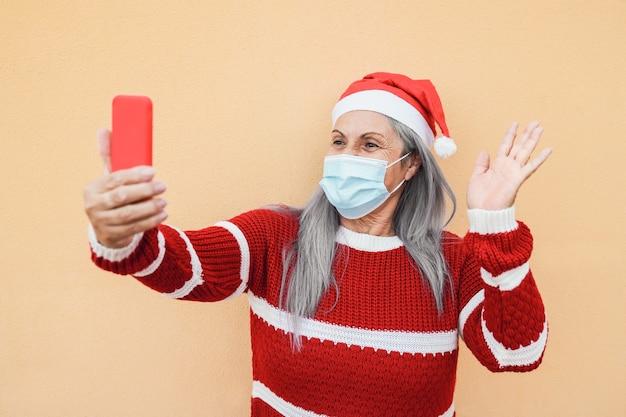 Счастливая старшая женщина, имеющая видеозвонок на мобильном телефоне в шляпе санта-клауса