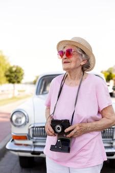 旅行中にカメラを持って幸せな年配の女性