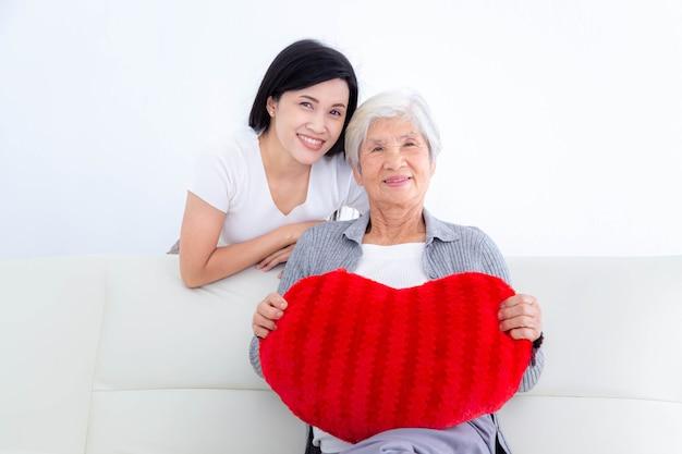 彼女の娘がソファに座って赤いハートの枕を保持している幸せな年配の女性。母の日おめでとう。幸せな家族の概念