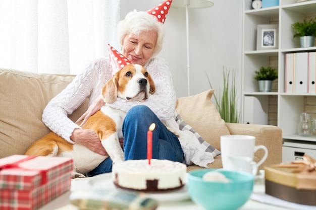 Happy senior woman hugging dog on birthday