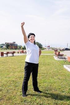 팔을 위로 서 공원에서 운동하는 스포츠 옷에 행복 수석 여자