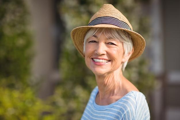 Счастливая старшая женщина в соломенной шляпе