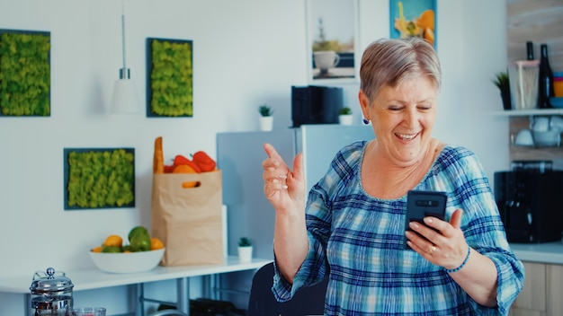 Breakfsatの間にスマートフォンでキッチンで音楽を聞いている幸せな年配の女性。リラックスした高齢者のダンス、最新技術による楽しいライフスタイル