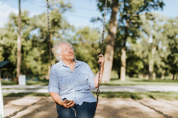 Happy senior woman listening to music on a swing