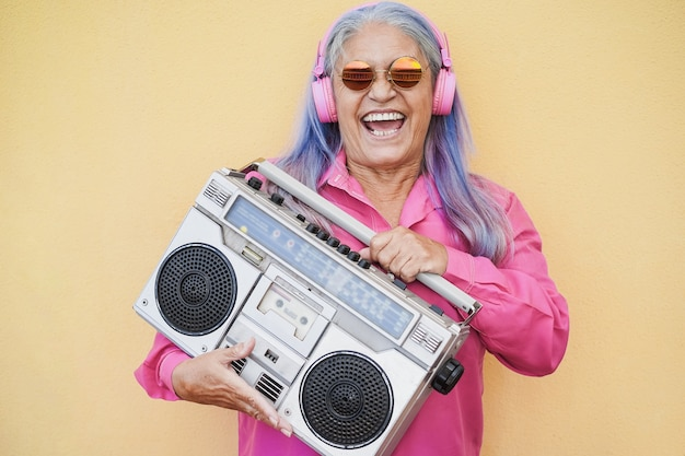 Happy senior woman listening music while holding boombox vintage stereo - focus on face