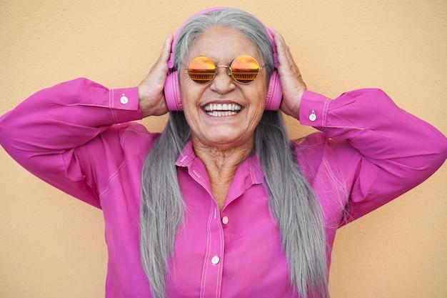 ヘッドフォンでプレイリストの音楽を聴いて幸せな年配の女性