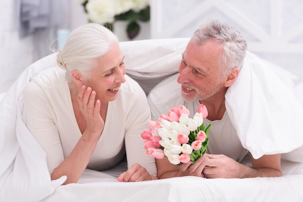Happy senior woman lying on bed looking at tulip flowers held by her husband