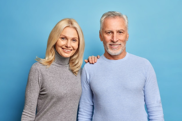 Happy senior woman and man express positive emotions pose together being still in love isolated over blue wall