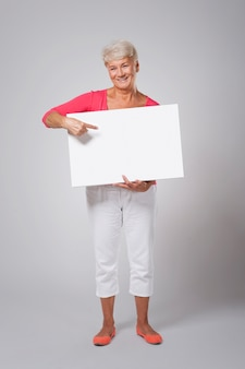 Happy senior woman pointing at whiteboard